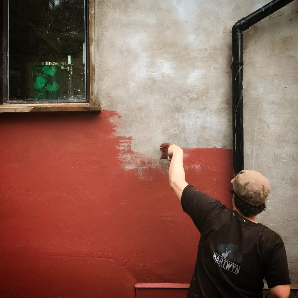 strong colour being painted onto straw bale house